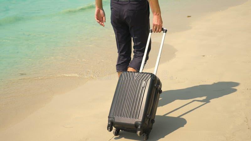 Um homem novo nas calças e em uma camisa clássica com uma mala de viagem anda ao longo da praia contra o contexto do mar de turqu fotografia de stock