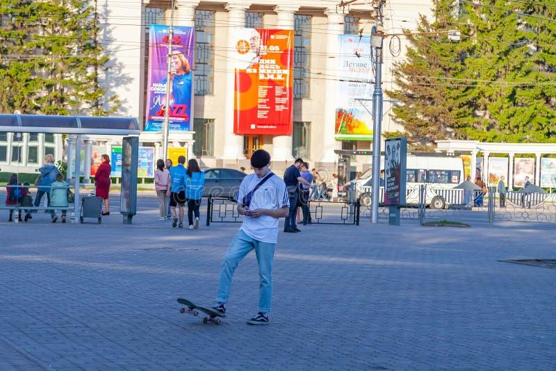 Um homem novo no t-shirt e na calças de ganga brancos está estando no quadrado para andar no parque com o um pé que puxa em um sk fotografia de stock