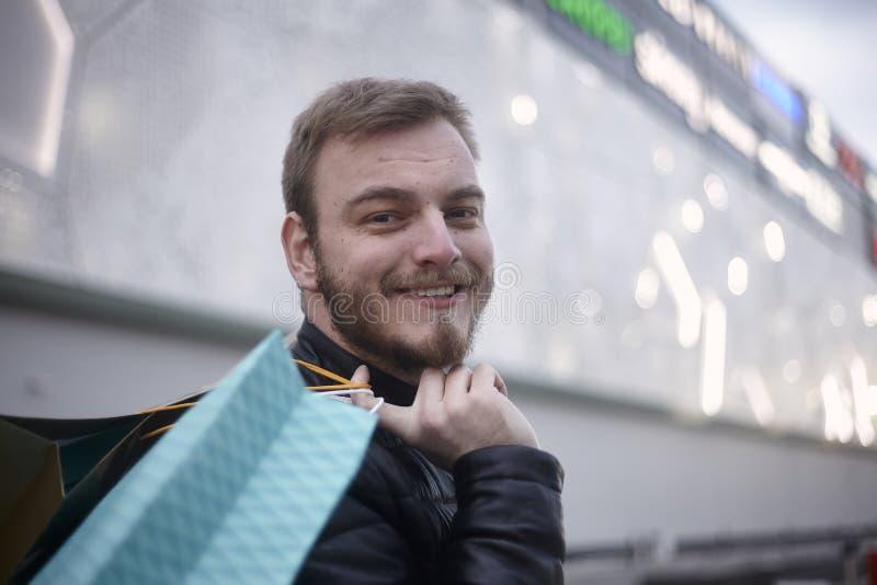 Um homem novo, olhando lateralmente à câmera, guardando sacos de compras na frente de um shopping com logotipos fora foto de stock