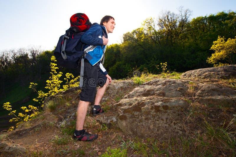 Um homem novo que caminha no curso da floresta, caminhada, backpacking, a fotografia de stock royalty free