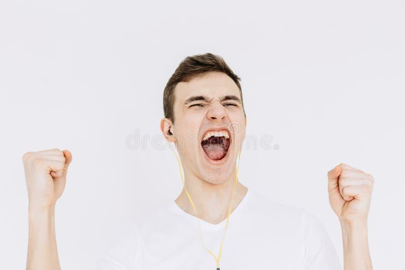 Um homem novo que grita ao escutar a música e ao apertar seus punhos Fundo branco isolado imagem de stock