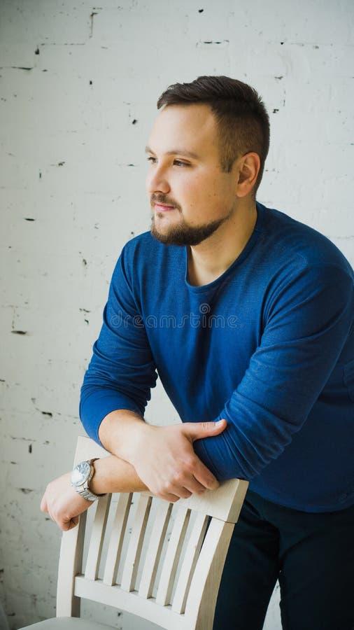 Um homem novo que inclina-se na parte de tr?s de uma cadeira olha ao lado contra uma parede de tijolo branca imagens de stock