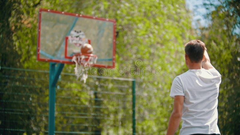 Um homem novo que joga a bola na aro e na ela de basquetebol obtém no alvo fotografia de stock royalty free