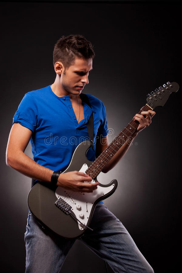Um homem novo que joga a guitarra com grandes emoções imagem de stock