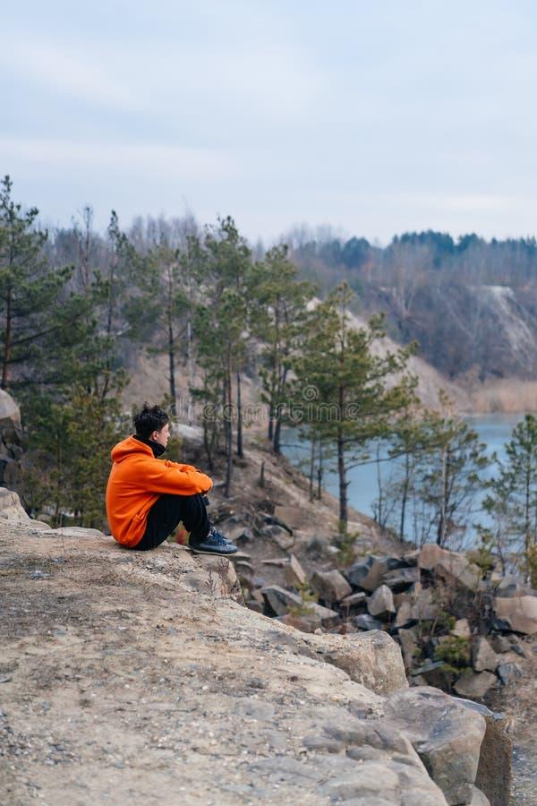 Um homem novo que senta-se na borda de um penhasco levanta para a câmera foto de stock royalty free