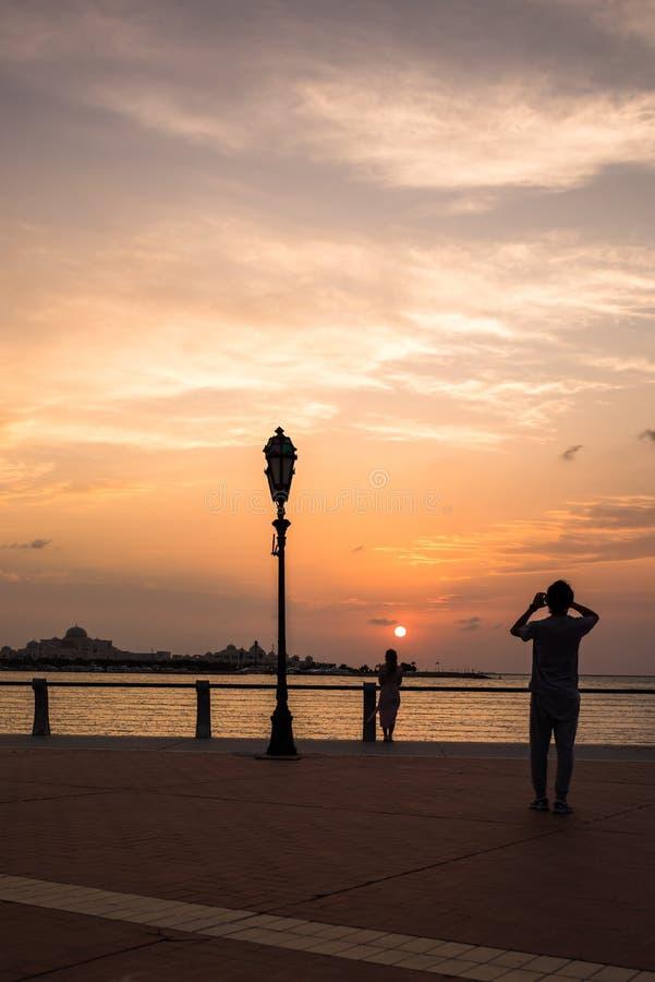 Um homem novo que toma a imagem de sua amiga durante o por do sol nebuloso em Corniche Abu Dhabi, UAE imagem de stock royalty free