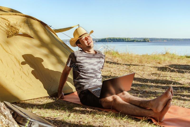 Um homem novo que trabalha e que descansa na natureza Um homem em um chapéu que senta-se na natureza perto da barraca com um port imagem de stock