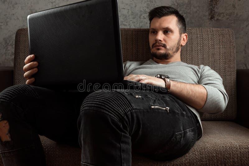 Um homem novo que trabalha em um port?til que relaxa em um sof? confort?vel em casa nas cal?as de brim O conceito de freelancing, imagens de stock