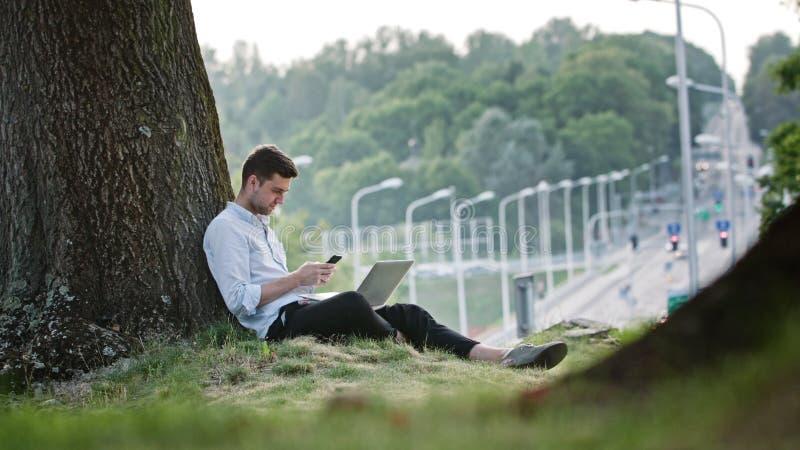 Um homem novo que usa um móbil e um portátil fora fotografia de stock royalty free