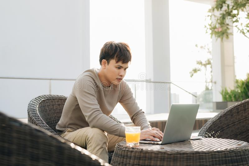 Um homem novo que usa o laptop ao sentar-se em um sofá fora imagens de stock royalty free
