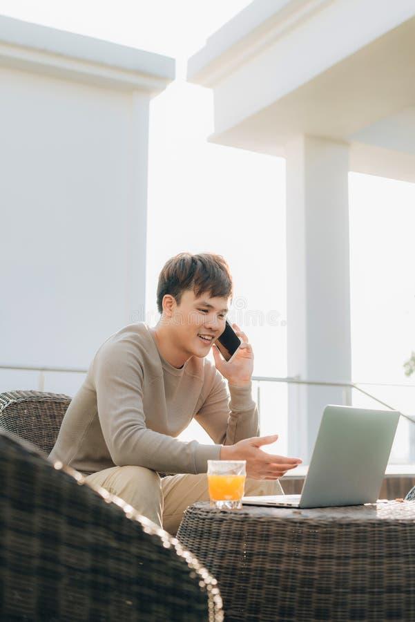 Um homem novo que usa o laptop ao sentar-se em um sof? fora fotografia de stock royalty free