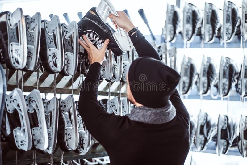 Um homem novo que veste a roupa morna que está ao lado de uma cremalheira e que escolhe um par de patins em um vestuário fotografia de stock