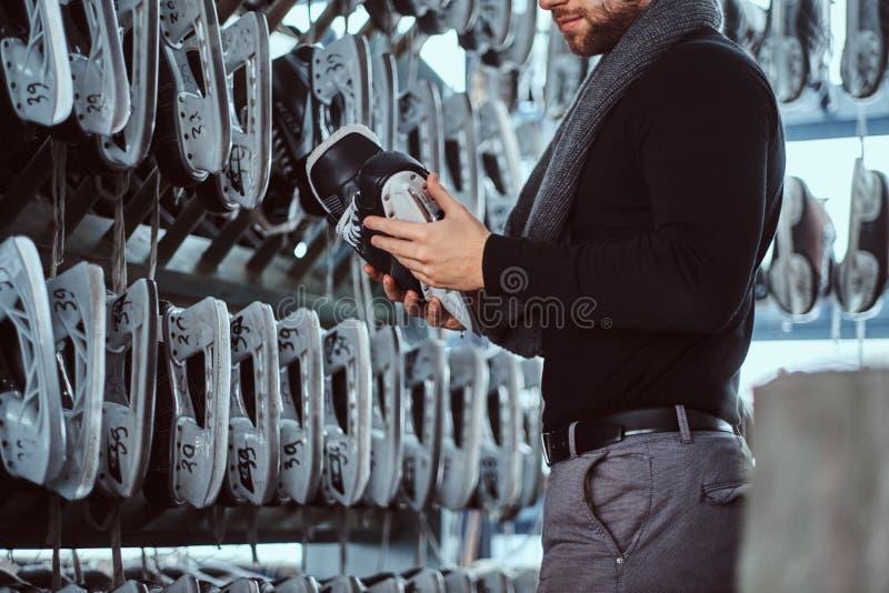 Um homem novo que veste a roupa morna que está ao lado de uma cremalheira e que escolhe um par de patins em um vestuário imagem de stock royalty free