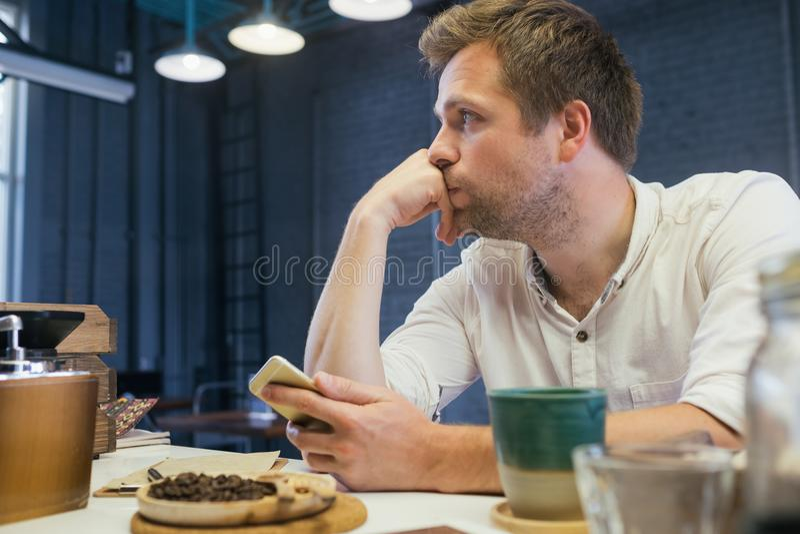 Um homem novo senta-se em um café e espera-se um sócio comercial na solidão fotografia de stock