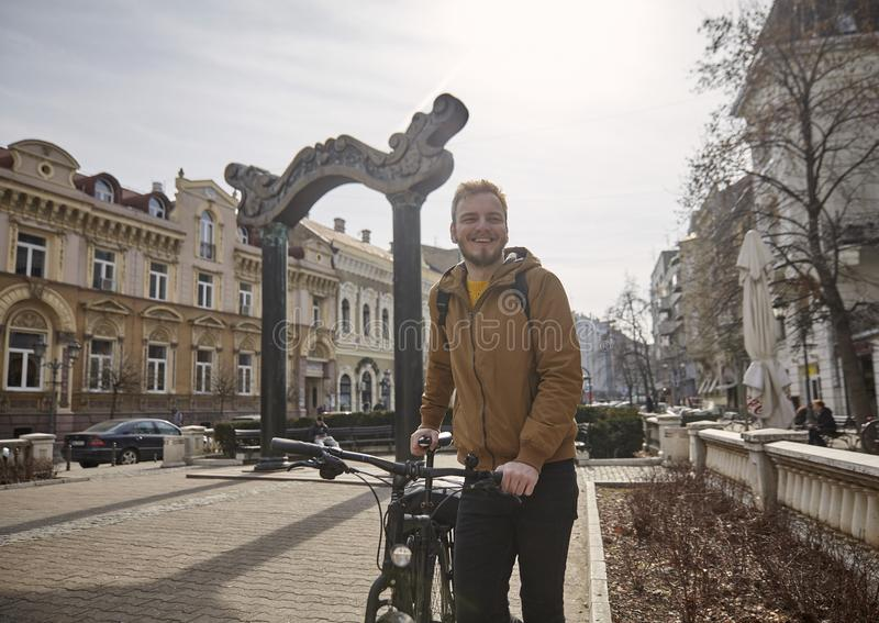 Um homem novo, sorrindo e feliz, guardando e levantando com sua bicicleta estando em um quadrado de cidade velho, em tradicional  fotografia de stock royalty free