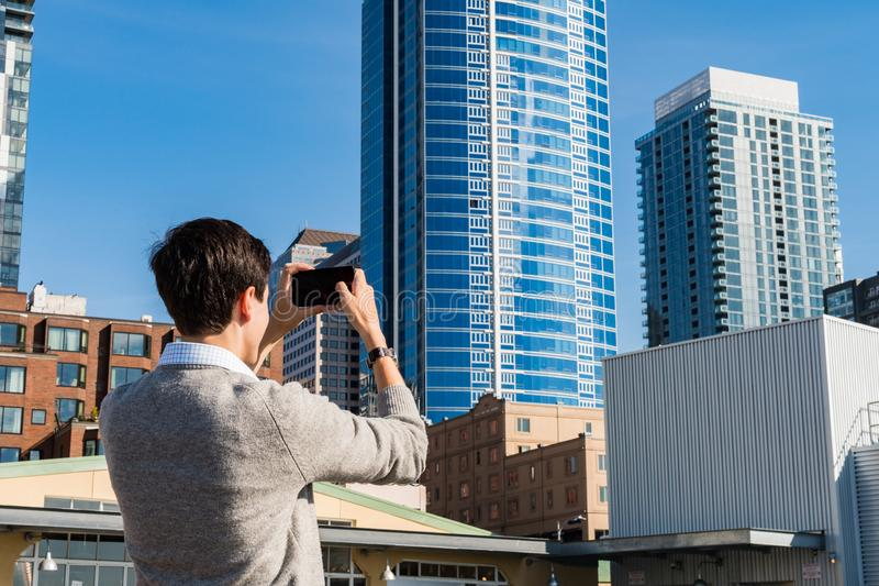 Um homem novo toma fotografias com seu telefone celular das construções fora do mercado de Pike em Seattle imagens de stock royalty free