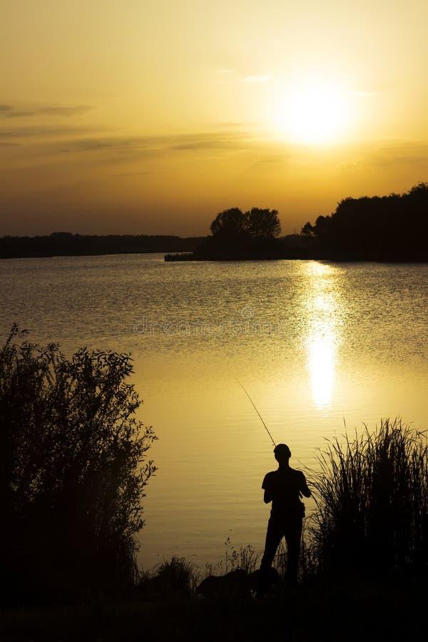 Um homem novo trava peixes no lago no por do sol Reflexão bonita do sol na água Abrandamento fotos de stock