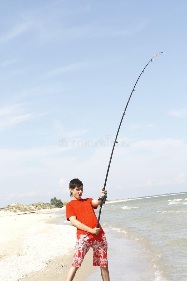 Um homem novo trava um peixe foto de stock royalty free
