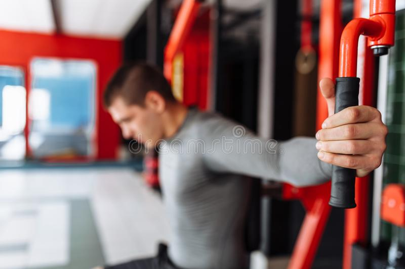 Um homem novo treina no gym, agita no tríceps e no bíceps do gym fotografia de stock