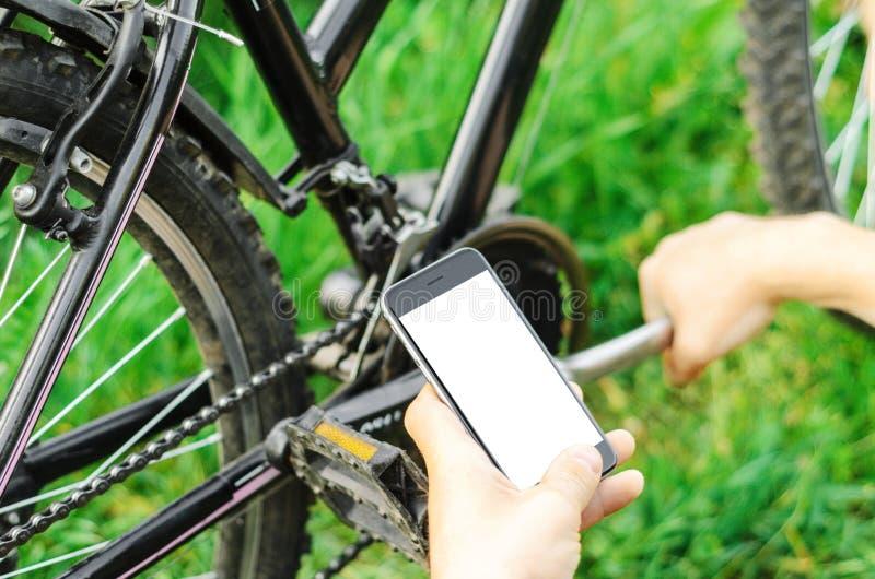 Um homem olha no telefone, reparando um Mountain bike em uma estrada de floresta Trabalho do reparo, mecânico foto de stock