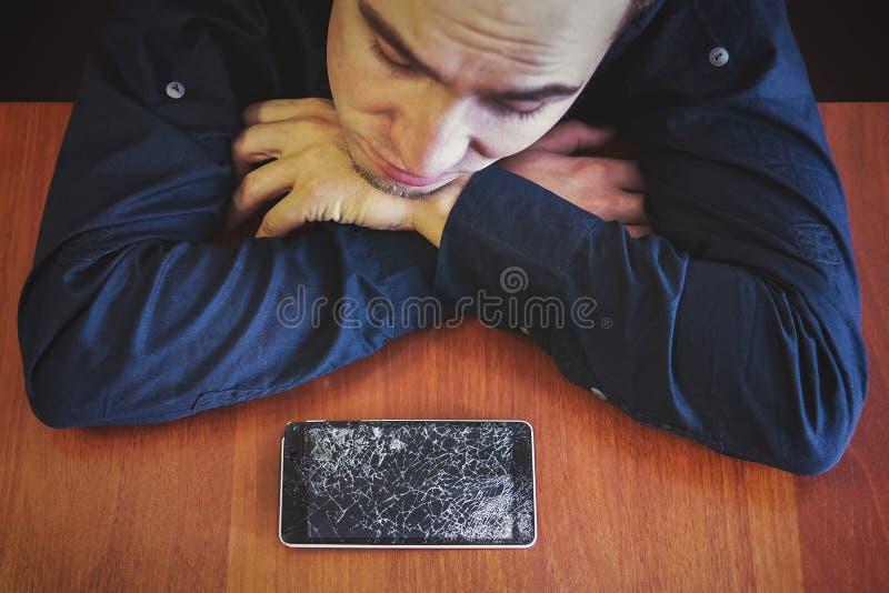 Um homem olha seu telefone quebrado que encontra-se em uma tabela de madeira com um olhar triste fotos de stock