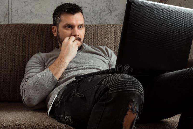 Um homem olha um vídeo em um portátil ao se sentar no sofá é surpreendido muito Vídeos da pornografia do conceito, admiração, des foto de stock