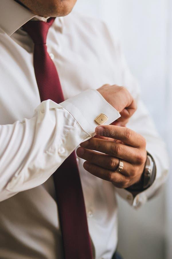 Um homem ou um homem de negócios em um laço vermelho fecham suas mãos com um botão de punho do ouro em uma camisa branca imagens de stock royalty free