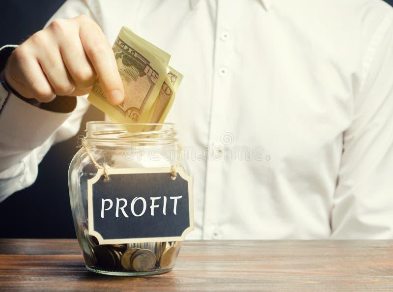 Um homem põe dólares em um frasco de vidro com o lucro da palavra Conceito do sucesso comercial, do crescimento financeiro e da r fotografia de stock