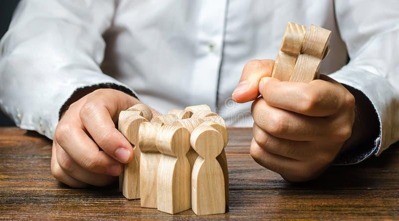 Um homem pega uma figurina de pessoas da multidão Contratação de funcionários Segmentação do mercado e niche conquista recursos h foto de stock royalty free