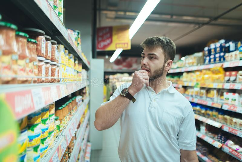 Um homem pensa que tipo do produto em um supermercado a escolher O comprador seleciona conservas alimentares na loja foto de stock royalty free