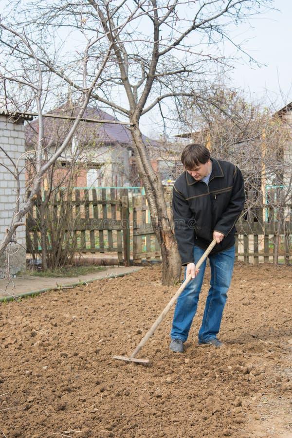 Um homem perto de sua casa afrouxa o ancinho para escavar acima um pedaço de terra fotografia de stock