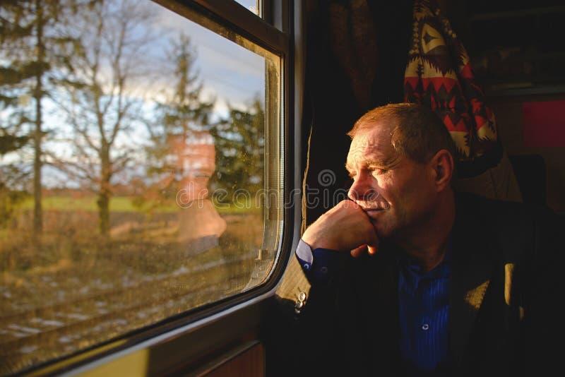 Um homem perto de uma janela em um trem imagem de stock