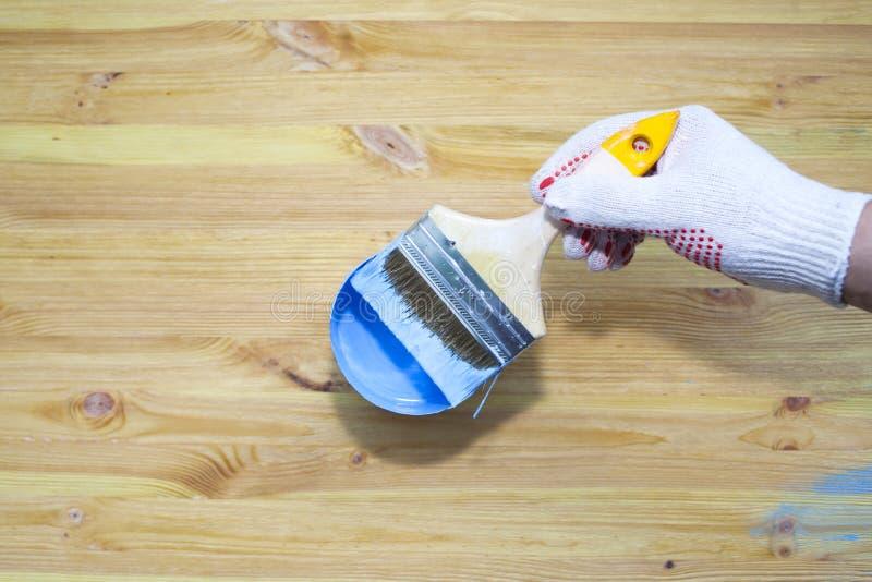 Um homem pinta manualmente uma superf?cie de madeira Escova com pintura azul imagens de stock