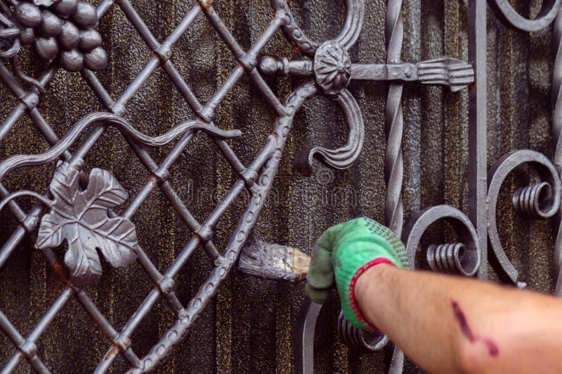 Um homem pinta uma porta com elementos forjados Em sua mão está uma luva verde, perto do cotovelo de uma pastagem imagem de stock