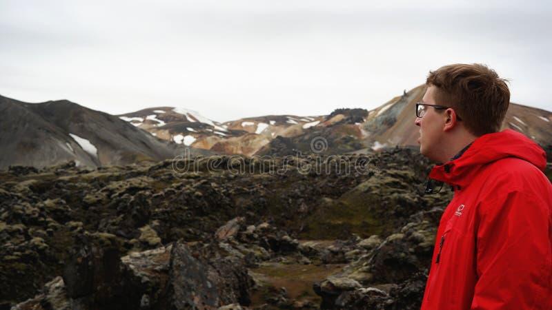 Um homem por montanhas do arco-íris de Landmannalaugar fotos de stock