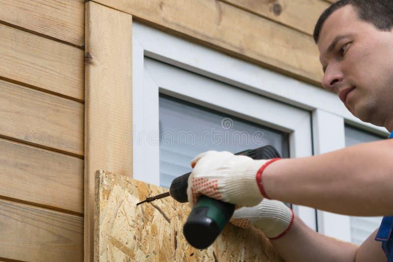 Um homem prende uma folha da madeira compensada para proteger as janelas das catástrofes naturais, close-up fotos de stock