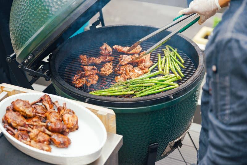 Um homem prepara a carne da galinha com aspargo grelhado para convidados, amigos Jantando o conceito da nutrição bufete Alimento fotos de stock