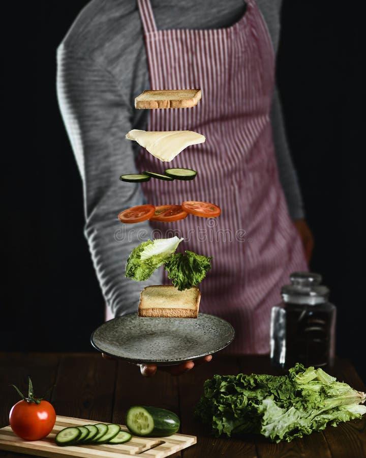 Um homem prepara os ingredientes para um sanduíche delicioso do vegetariano foto de stock