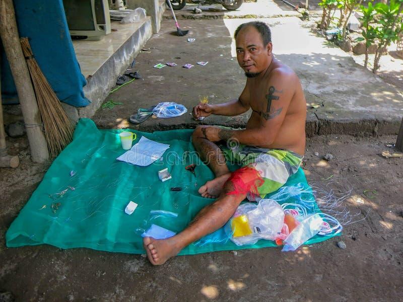 Um homem prepara-se à pesca O pescador produz o equipamento de pesca para travar a cavala Um método simples dos nativos Assento d ilustração do vetor