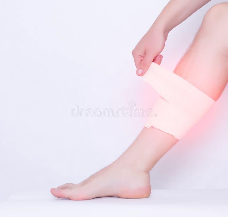 Um homem puxa uma atadura elástica em uma entorse do músculo de gastrocnemius em que dor e na inflamação, entorse do pé, branca foto de stock
