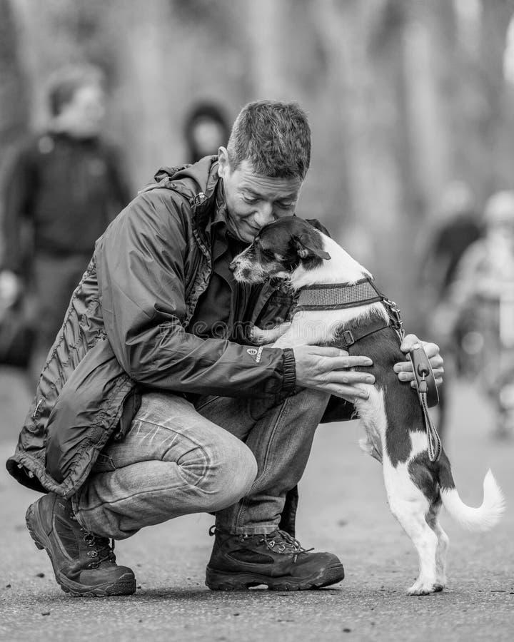 Um homem que abraça seu cão no parque em uma exposição de cães imagens de stock royalty free
