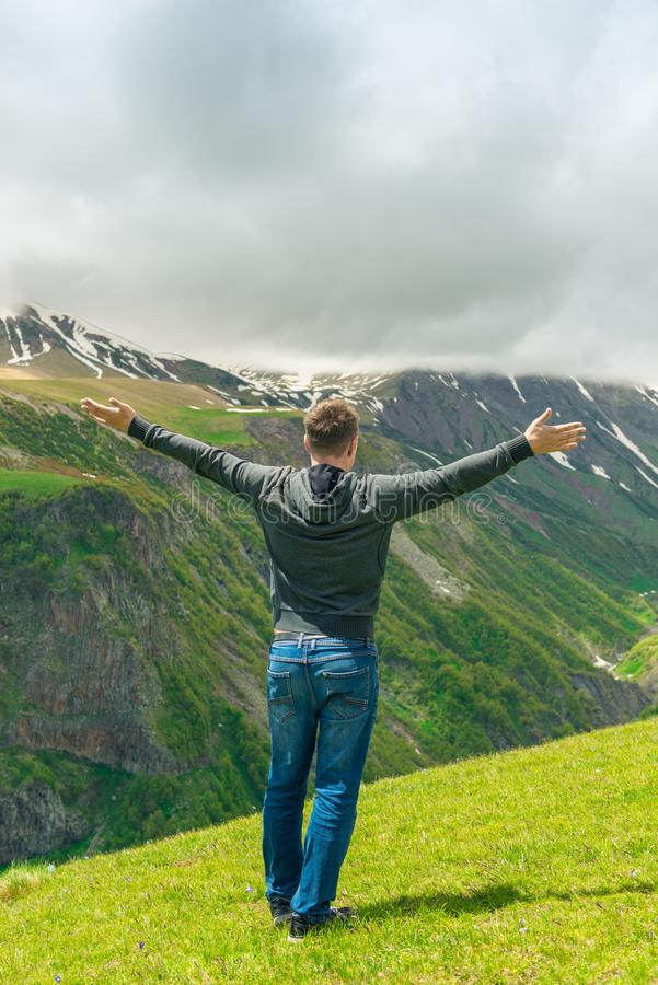 Um homem que admire os picos de montanha bonitos, vista da parte traseira imagem de stock royalty free