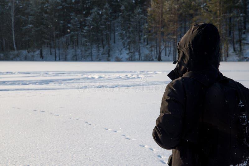 Um homem que anda na neve Silhueta de um homem que anda em uma planície nevado fotos de stock royalty free