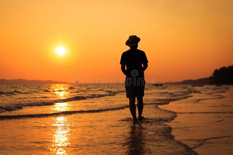 Um homem que anda na praia Viaje e relaxe o conceito fotografia de stock royalty free