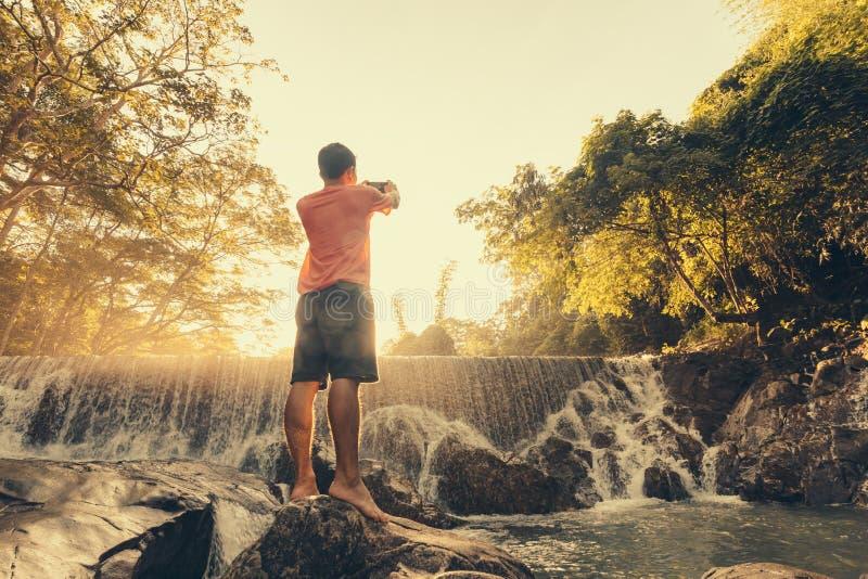 Um homem que aprecia cachoeira tropical surpreendente levantou as mãos viaja férias do estilo de vida e do conceito do sucesso fotografia de stock