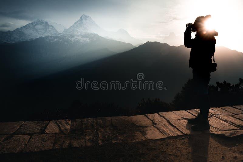 Um homem que bebe um chá durante o nascer do sol e cercado por montanhas imagens de stock royalty free