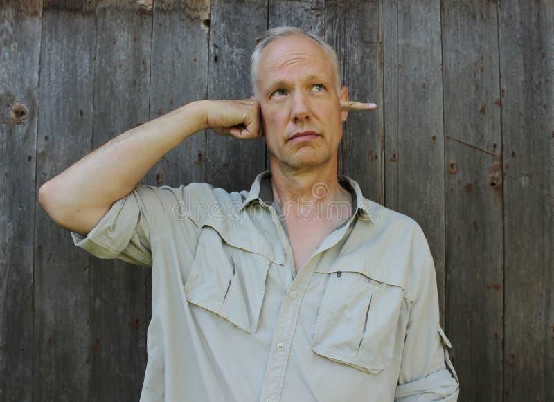 Um homem que cola seu dedo através de sua cabeça imagem de stock royalty free