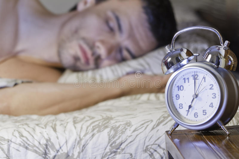 Um homem que dorme perto de um despertador retro foto de stock