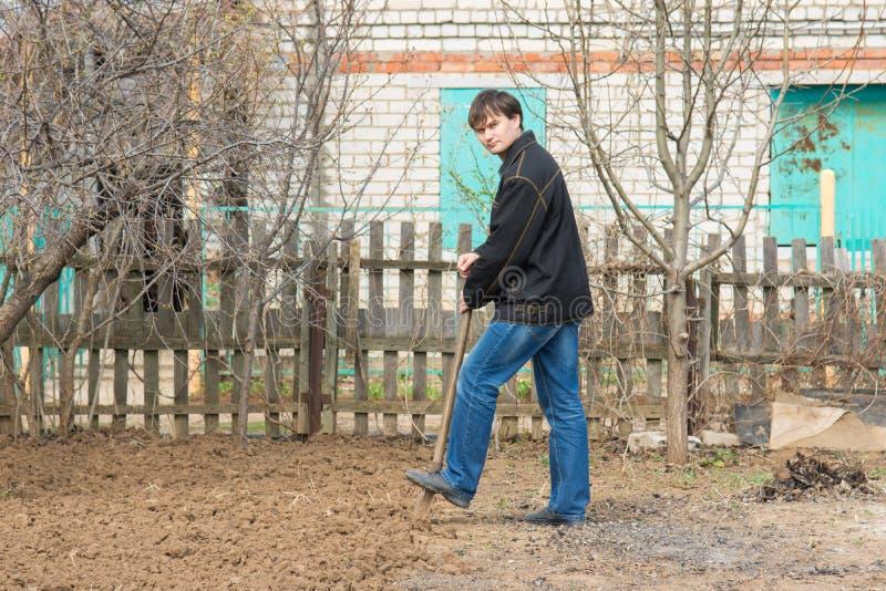 Um homem que está em um local do país com uma pá para escavar acima um pedaço de terra fotografia de stock royalty free