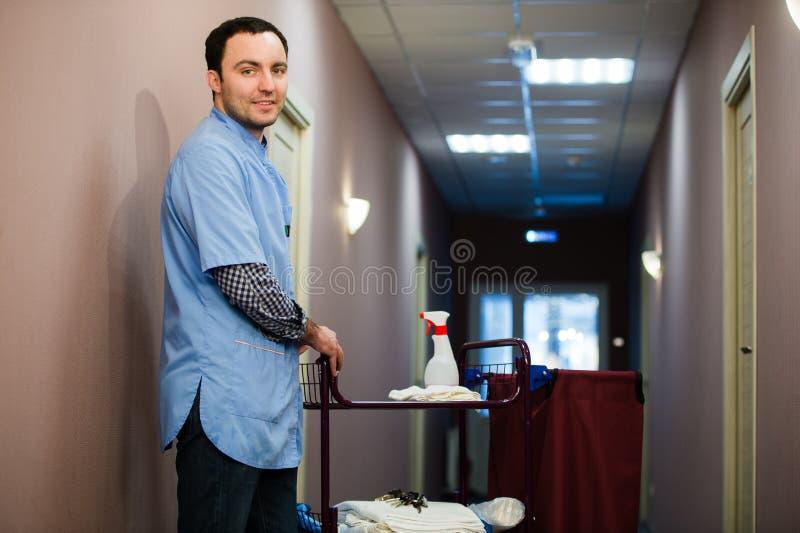 Um homem que esteja no pessoal do grupo de limpeza do hotel está sorrindo com um vácuo de toalha em processo de limpar as salas d fotos de stock royalty free